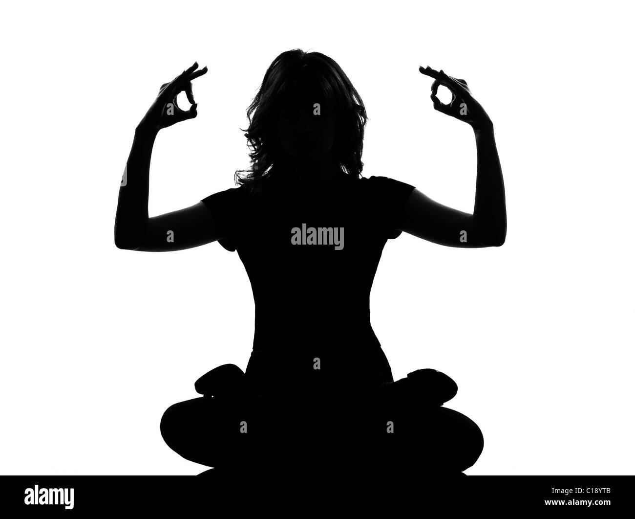 Silhouette pleine longueur dans l'ombre d'une jeune femme assise l'exercice de yoga Yoga au studio isolé Photo Stock