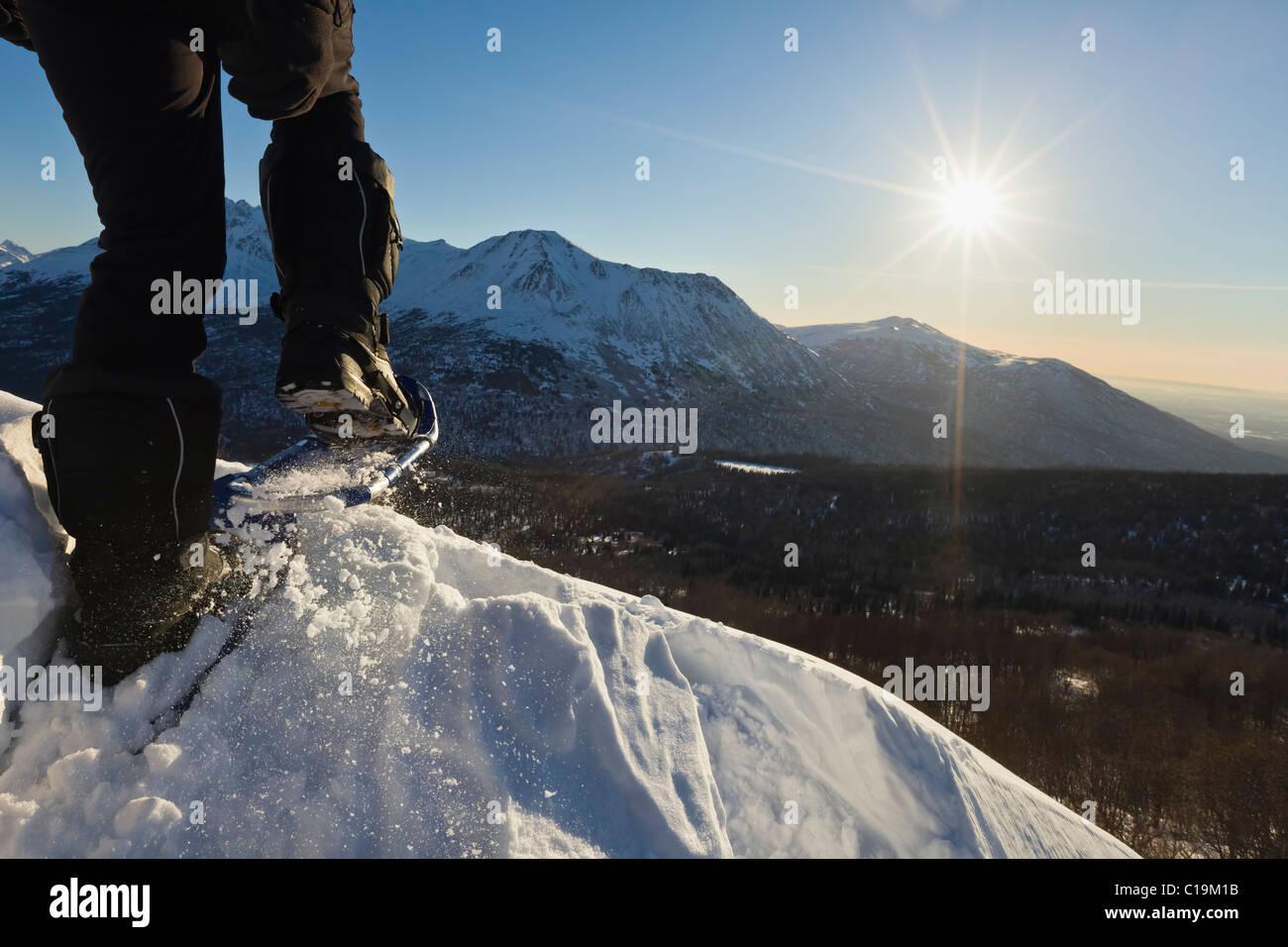 Un homme de la raquette sur une crête surplombant une vallée en Alaska avec soleil et montagnes en arrière Photo Stock