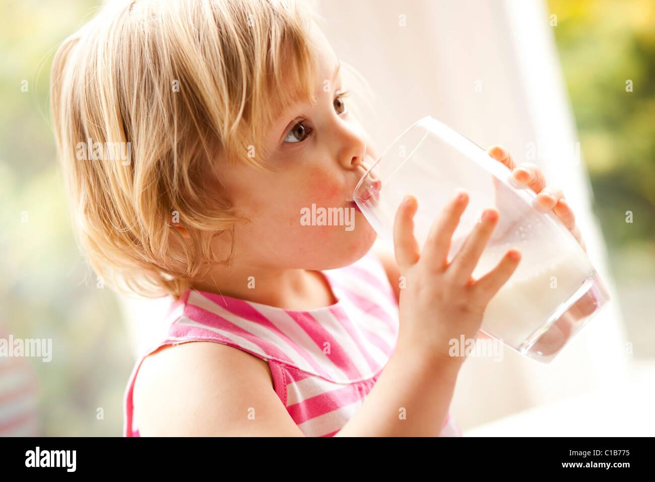 Enfant de boire dans un verre de lait Photo Stock