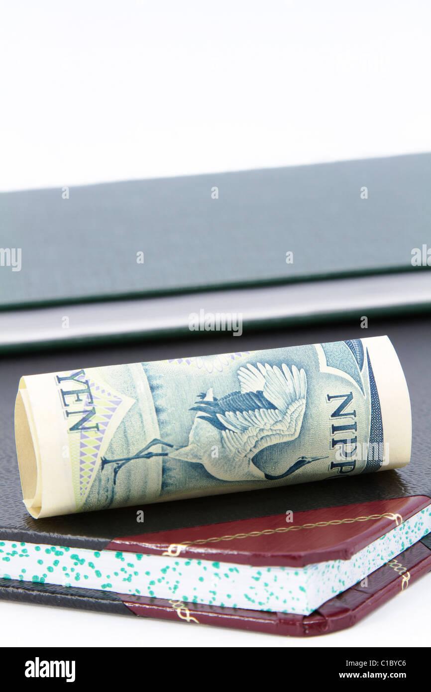 Yen, monnaie du Japon, se trouve sur le côté, sur un compte de l'espace au-dessus du grand livre; Photo Stock