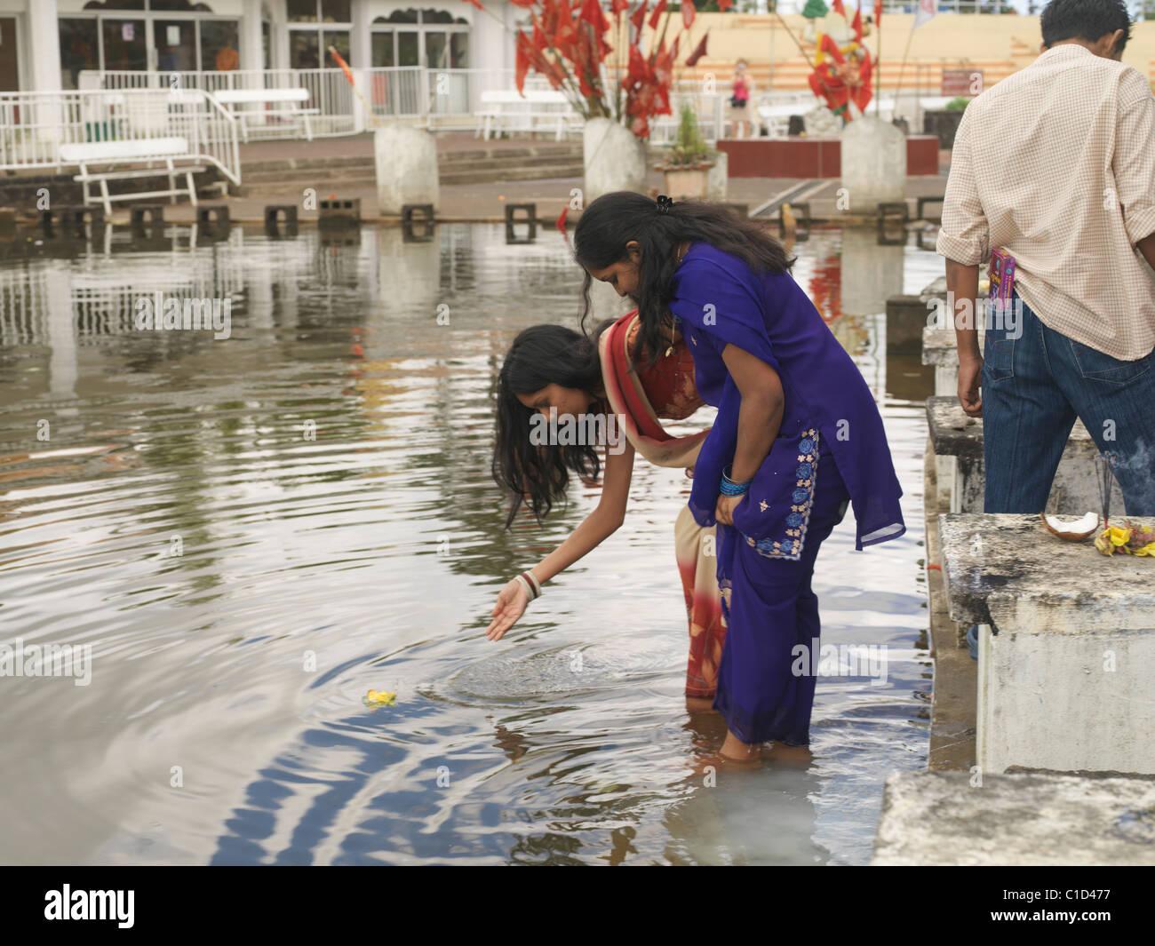 Ganga Talao Grand Bassin Maurice deux femmes pratiquer leur culte dans le lac avec des offres de fleurs Banque D'Images