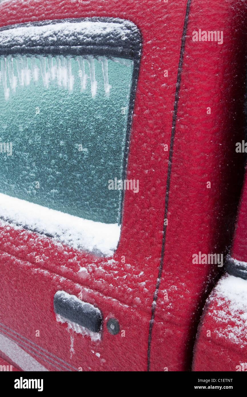 Recouvert de glace voiture rouge porte pendant la tempête de glace en hiver Photo Stock