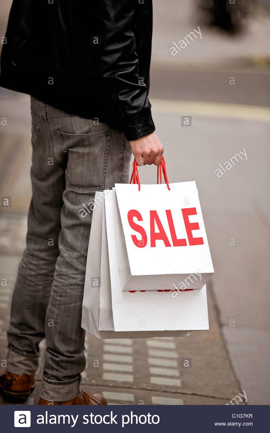 Un jeune homme tenant des sacs Photo Stock