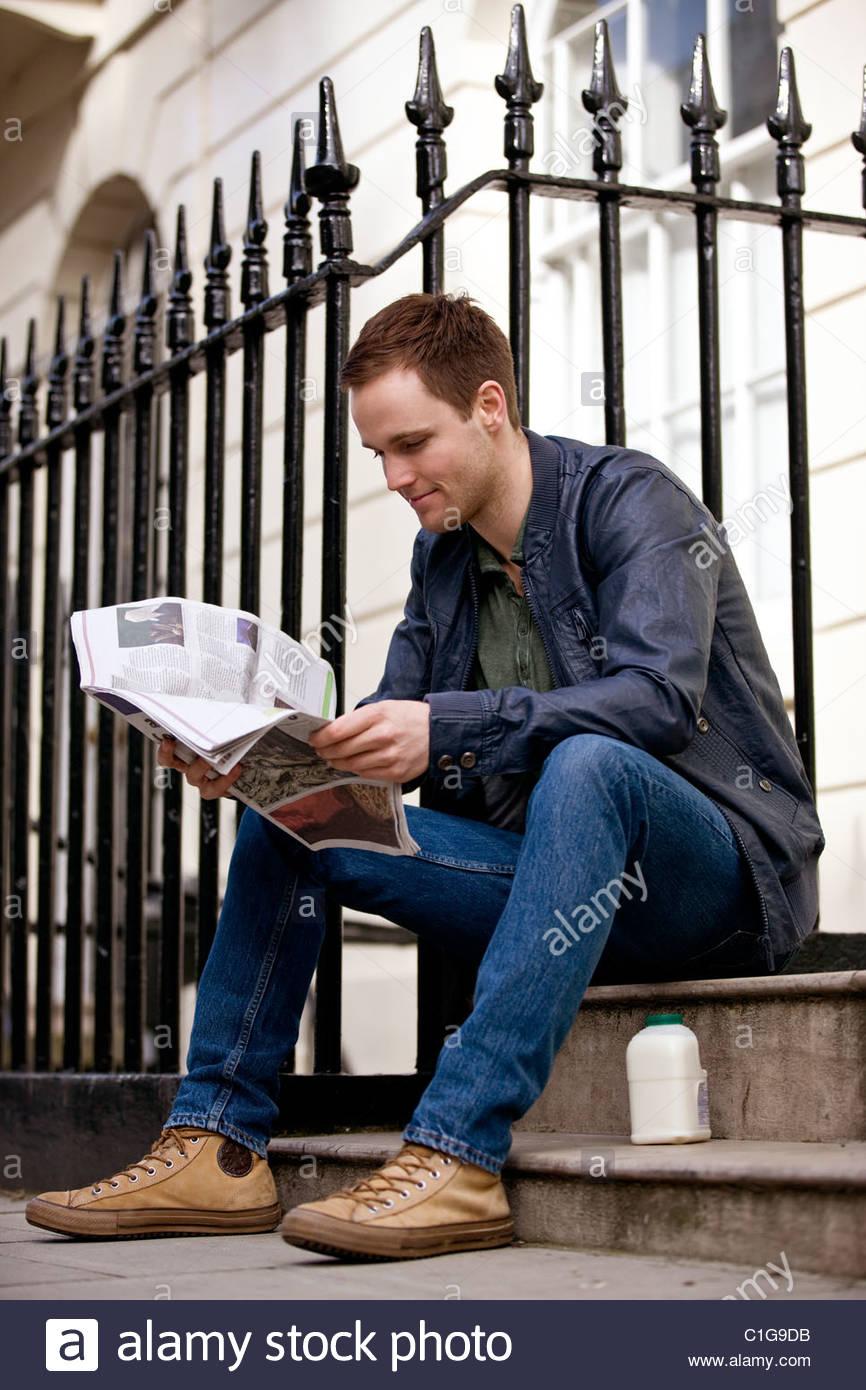Un jeune homme assis sur une étape, lire un journal Photo Stock