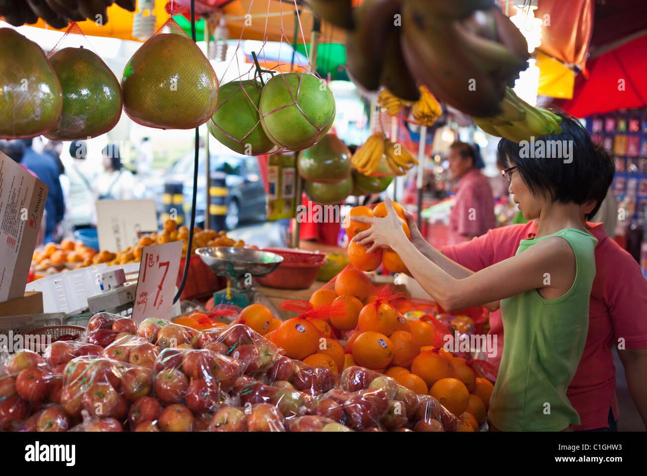 Woman shopping for fruit à Bugis Street Market. Bugis, Singapour Photo Stock