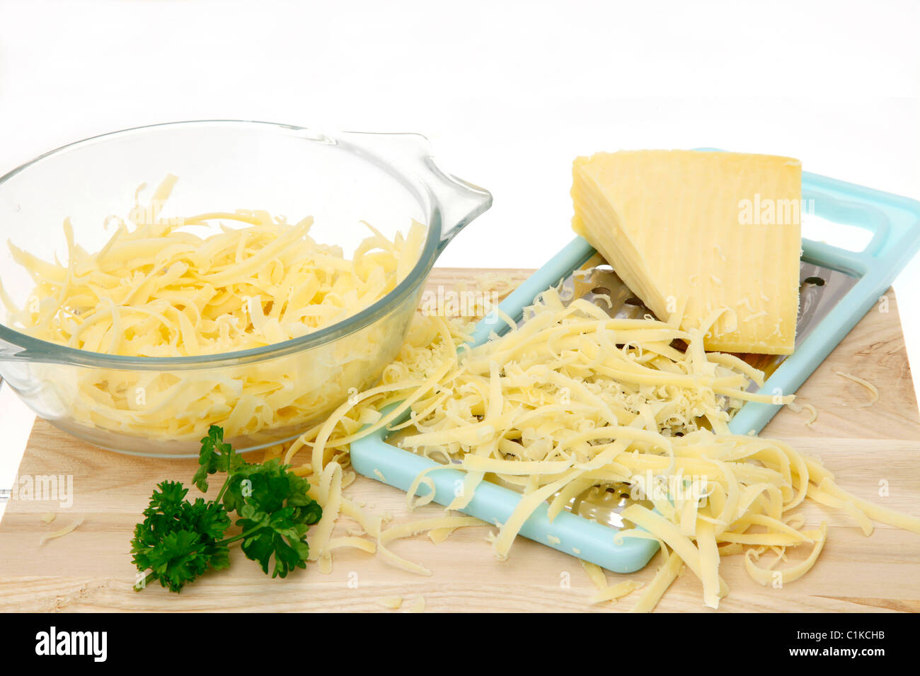 Le fromage râpé sur une planche à découper en bois - high key image Photo Stock