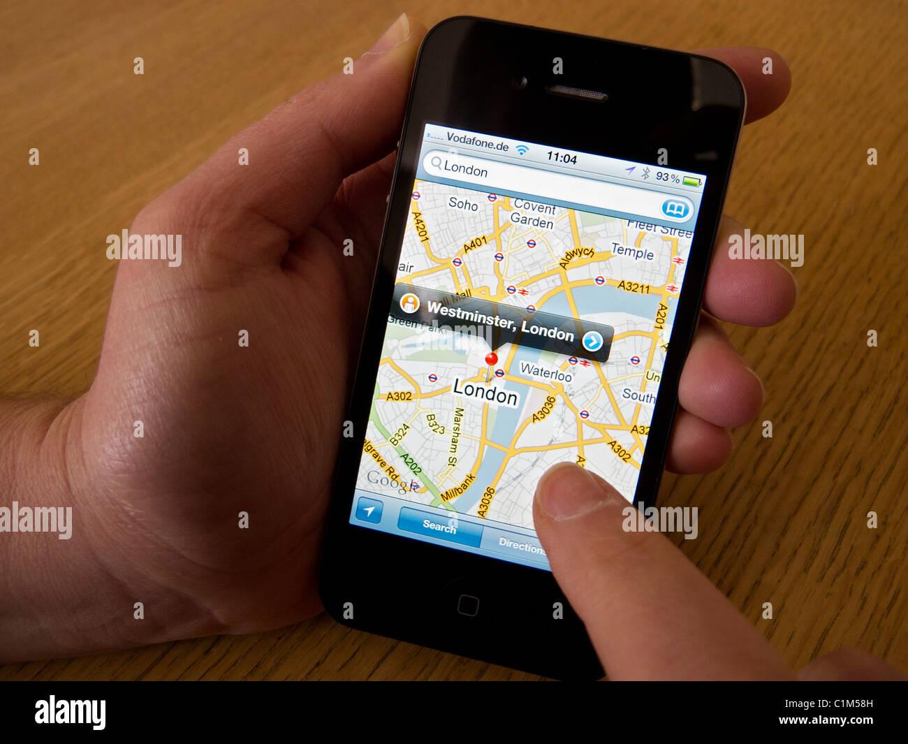 Woman looking at map of London sur Google Maps app pour Apple Iphone 4G Téléphone intelligent Photo Stock