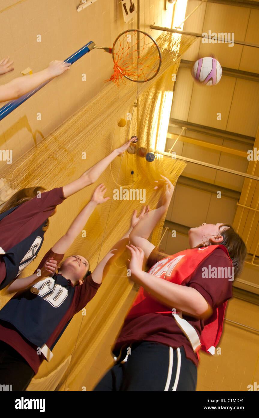 Quatre écolières jouant le netball dans un gymnase de l'école secondaire gymUK Photo Stock