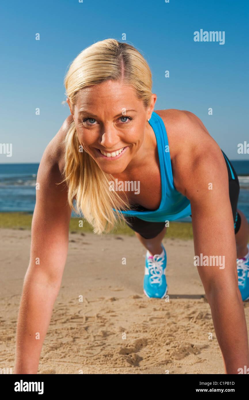Portrait de femme faisant des tractions sur beach Photo Stock