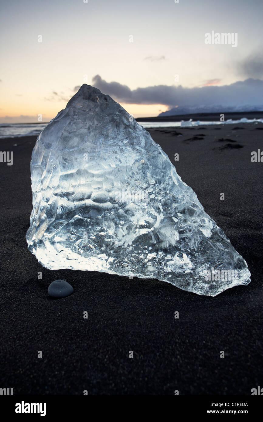 Les icebergs sur la plage avec la marée noire lave autour d'eux en Islande Banque D'Images