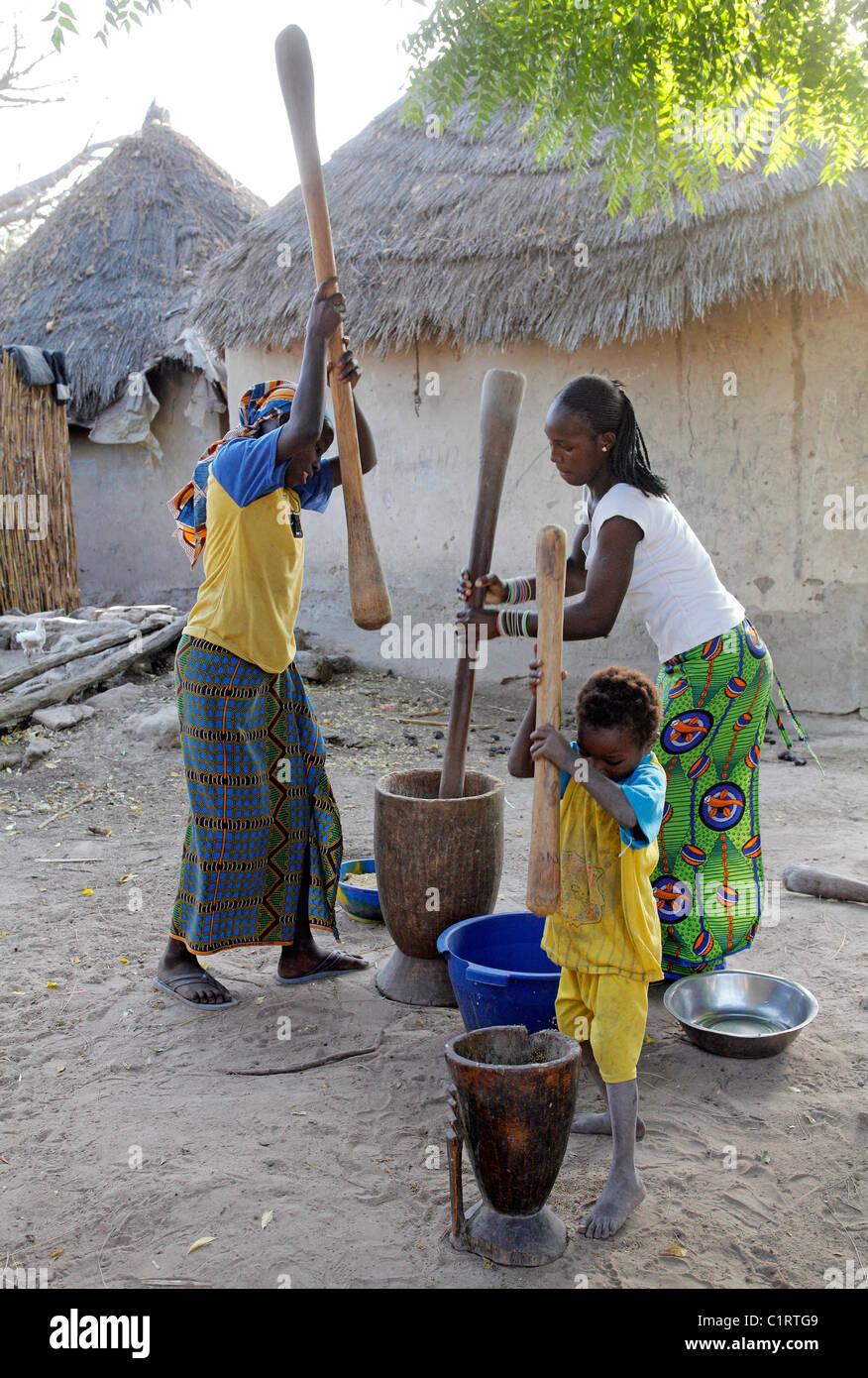 Femme et enfant battre le mil, maïs, sorgoum à l'aide de mortier et pestel. Sénégal Photo Stock
