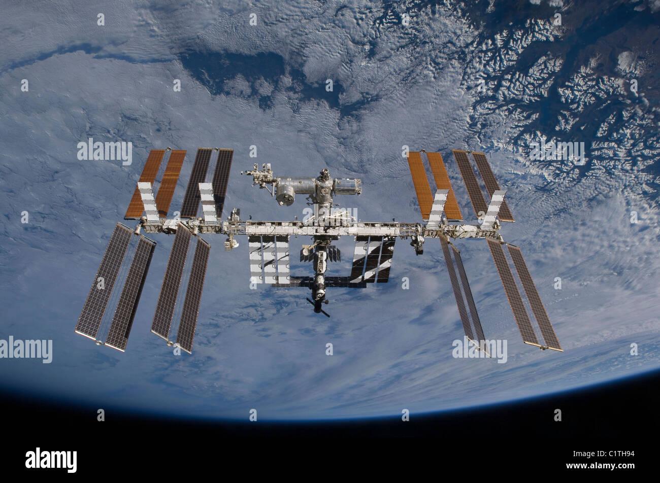 Station spatiale internationale pour toile de fond une nuée a couvert la terre. Photo Stock