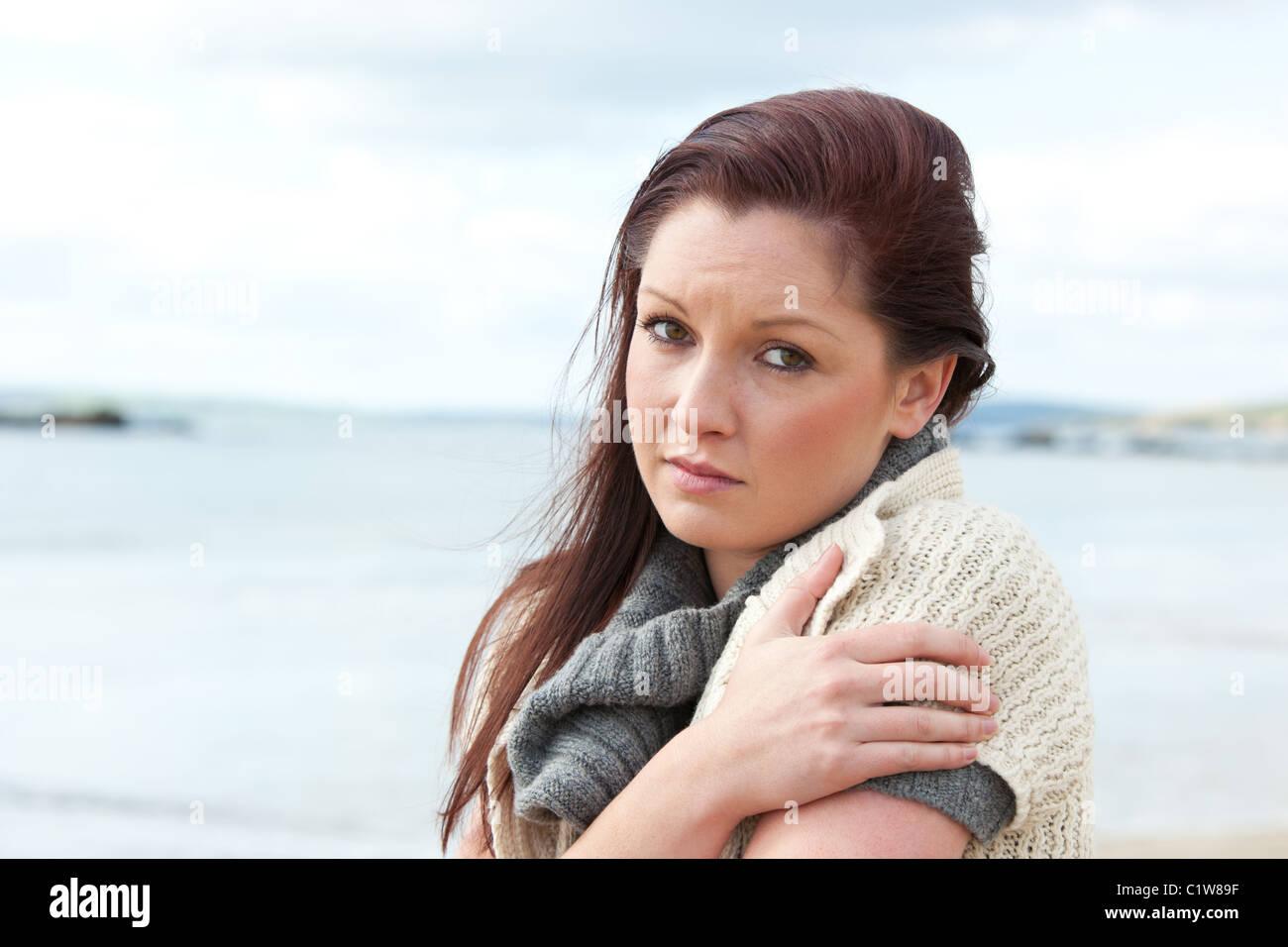 Downcast woman wearing hat and scarf sur la plage Photo Stock