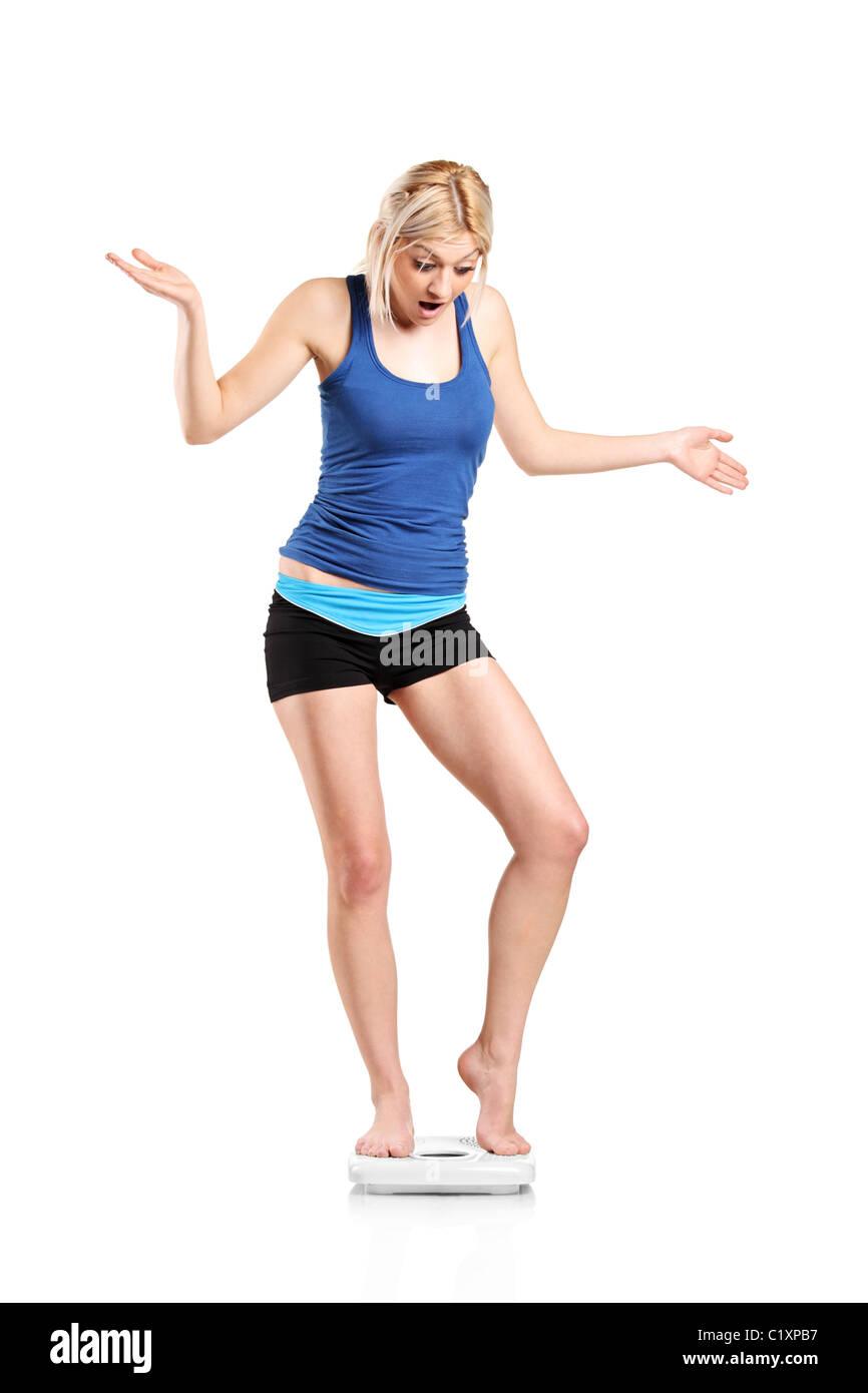 Une jeune femme déçue sur une échelle de poids Photo Stock