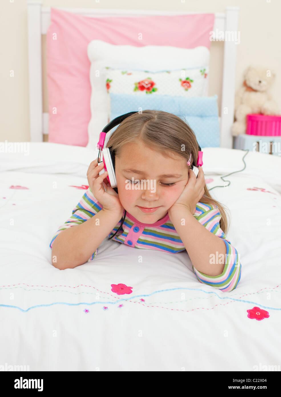 Beau petit gril à écouter de la musique allongée sur son lit Photo Stock