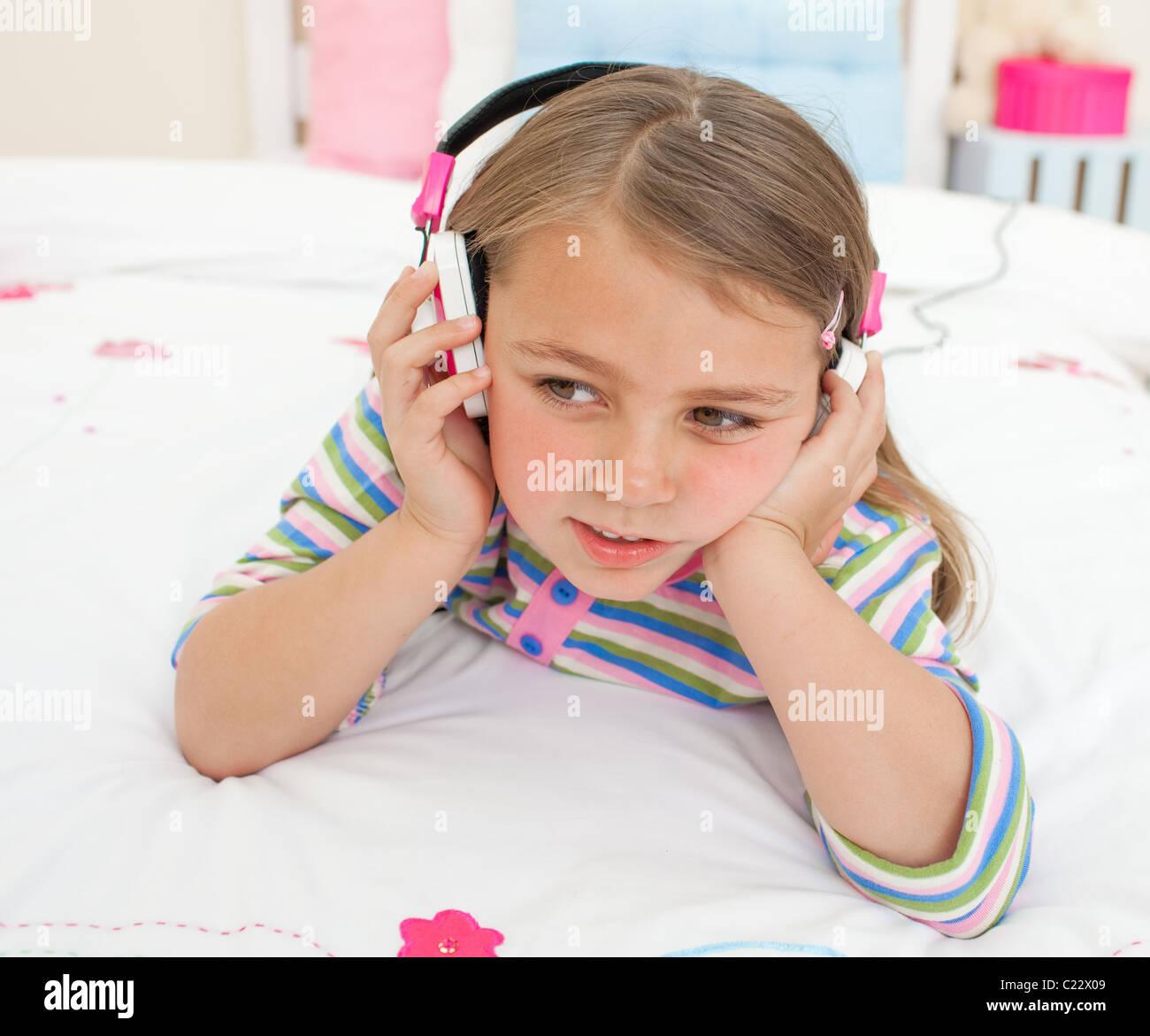 Gril adorable à écouter de la musique allongée sur son lit Photo Stock