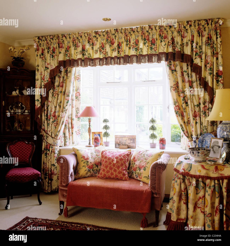 Petit canapé en face de la fenêtre avec des rideaux à motifs floraux et cantonnières correspondant Photo Stock
