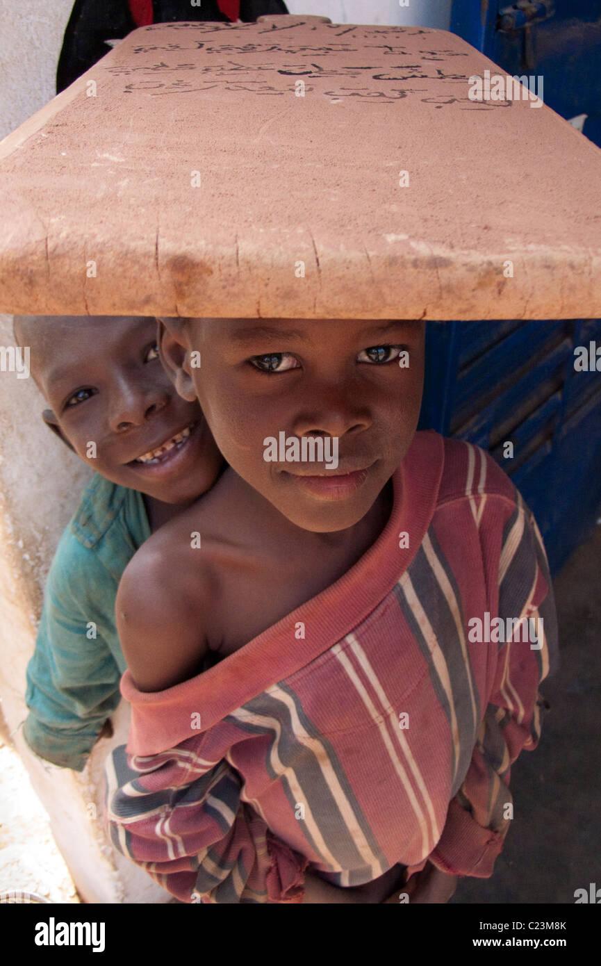 Tablette d'écolier portant sur sa tête dans l'Kibédoué quart de Bobo Dioulasso Photo Stock