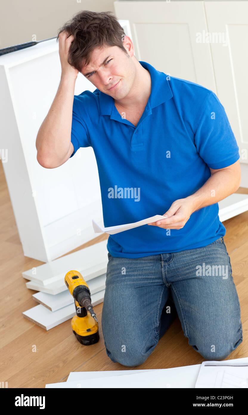 Homme Incomprehensive lire les instructions d'assemblage de meubles dans la cuisine Photo Stock