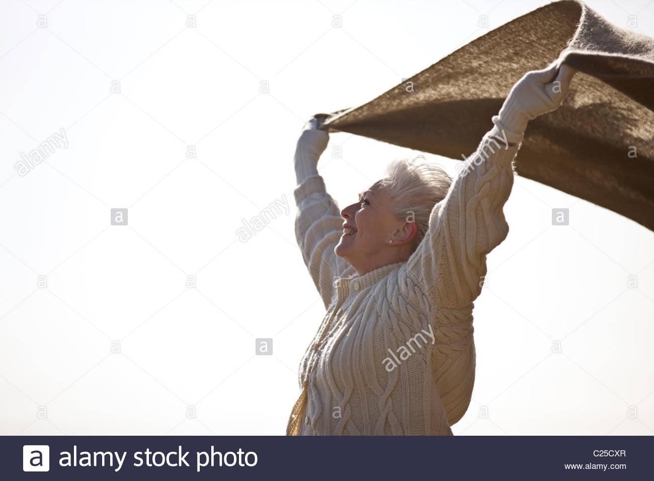 A senior woman holding une couverture dans le vent Photo Stock