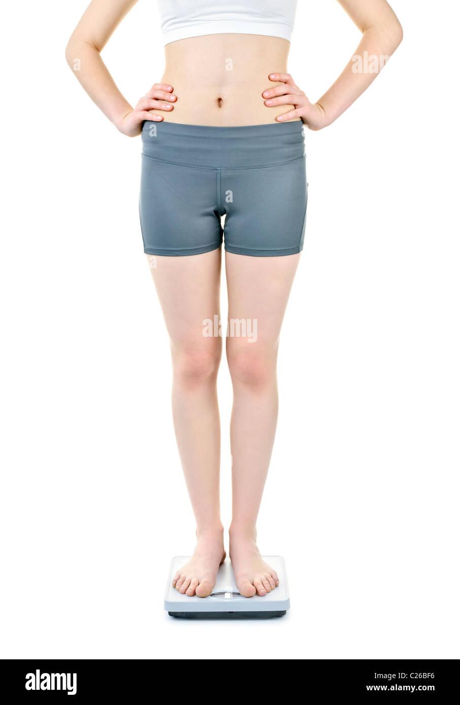 Santé de la jeune femme debout sur l'échelle de bain isolated on white Photo Stock