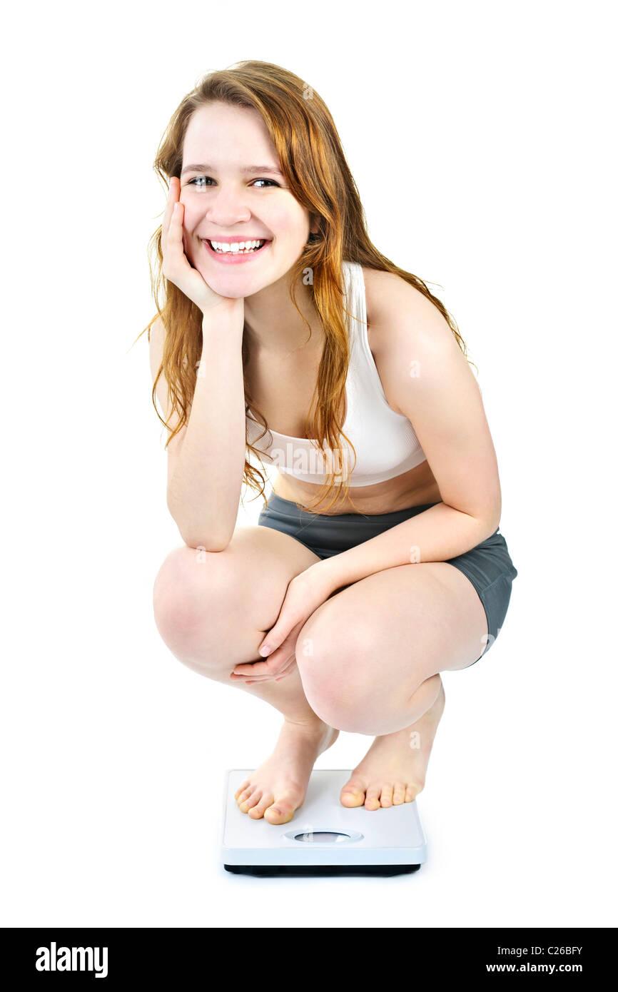 Heureux sain jeune femme accroupie sur balance de salle isolated on white Banque D'Images