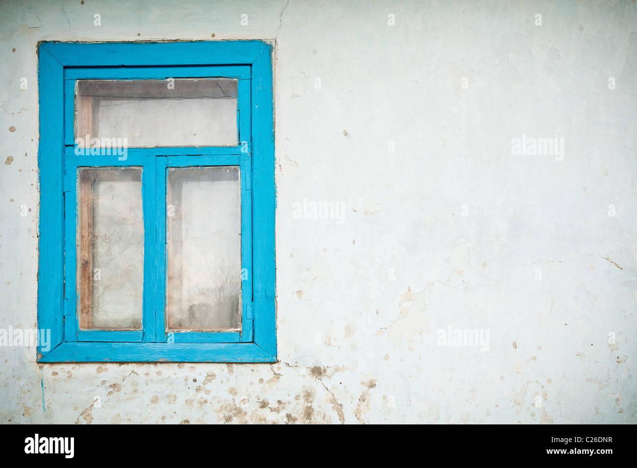 Vieux mur fissuré avec fenêtre peint avec blue Photo Stock
