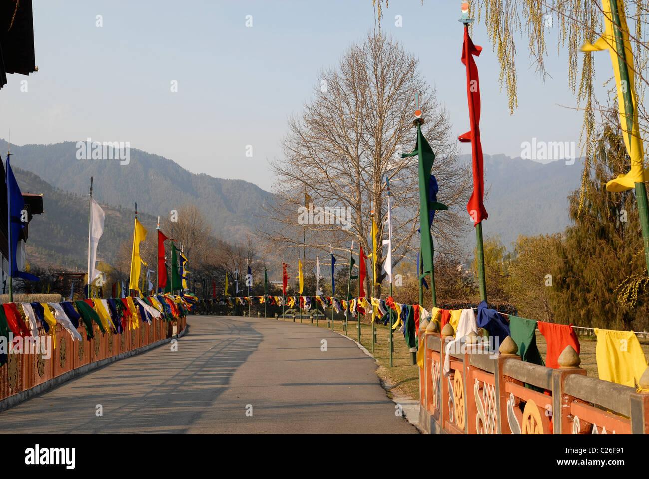 Route d'entrée à Trashi Chhoe Dzong, Thimphu, Bhoutan avec drapeaux au coucher du soleil la lumière Photo Stock
