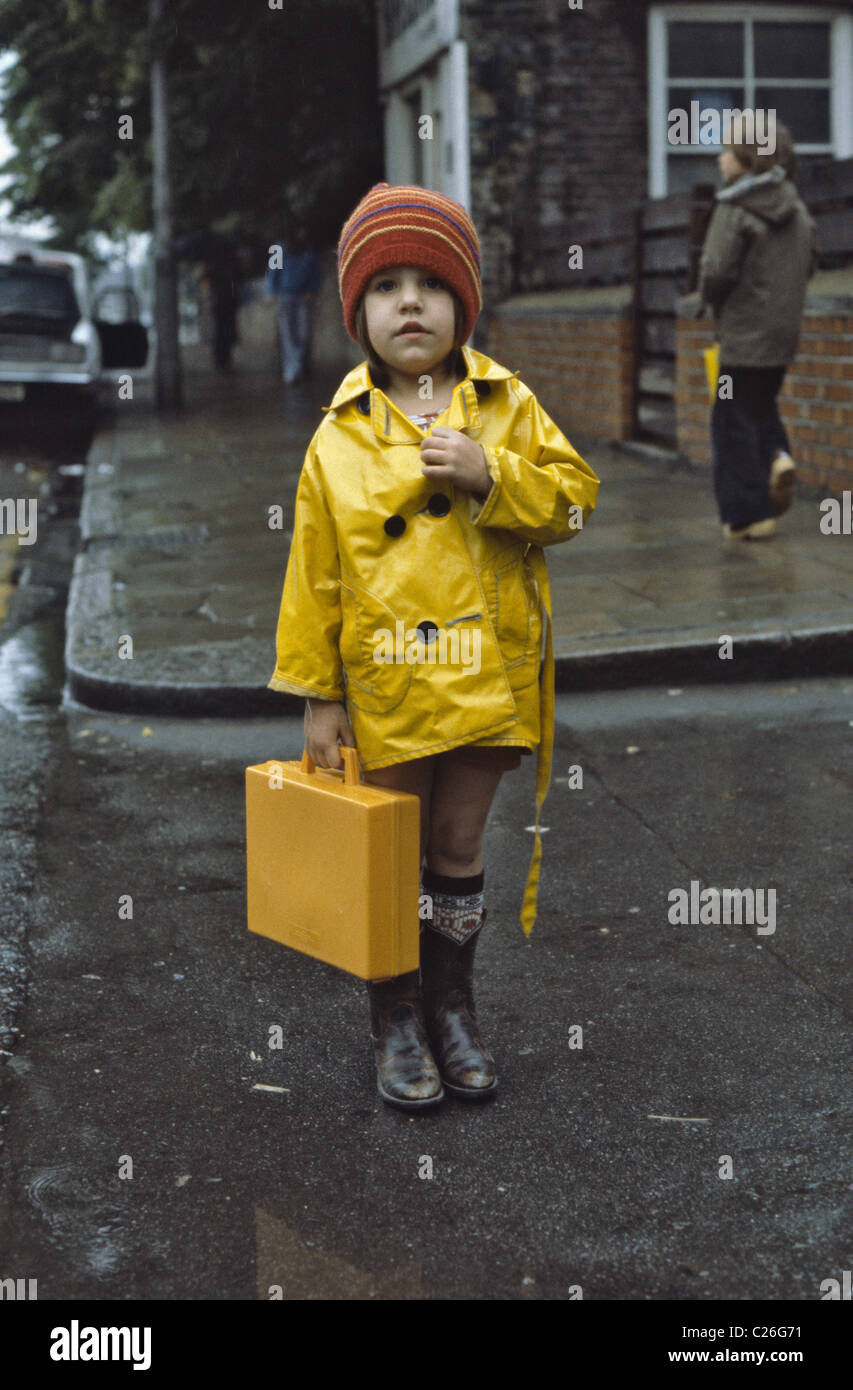 Young Girl wearing imperméable jaune tenant son cartable