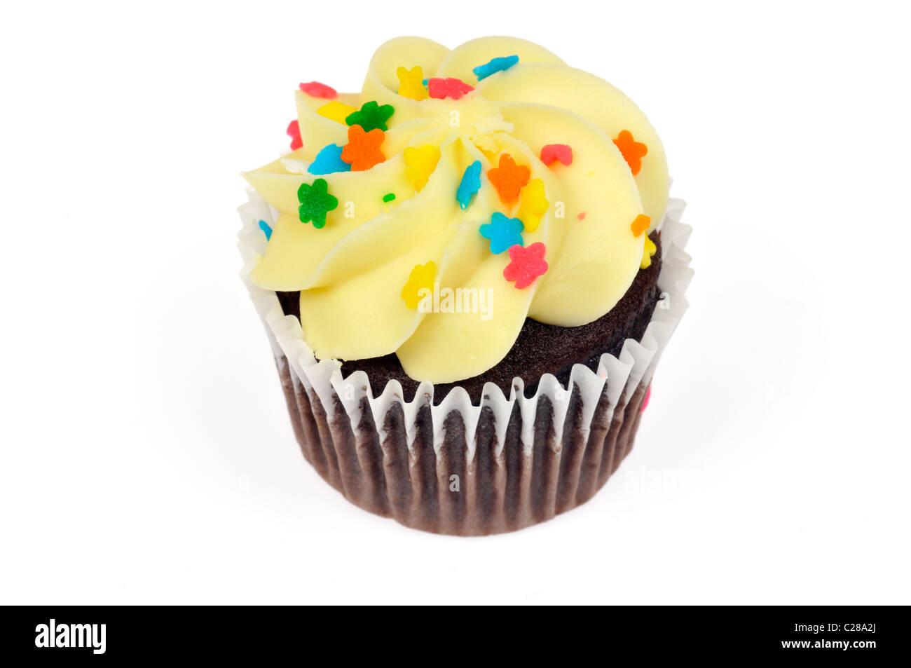 Cupcake chocolat décoré de glaçage au citron jaune et colorés sur fond blanc sprinkles cut out Photo Stock