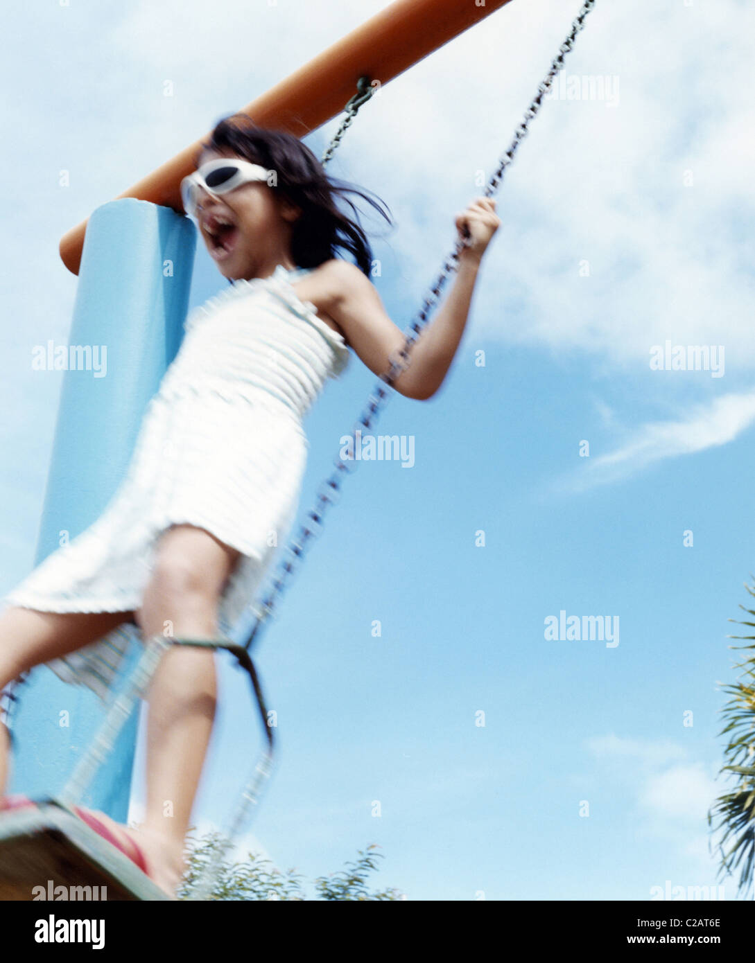 Girl playing on swing, low angle view Photo Stock