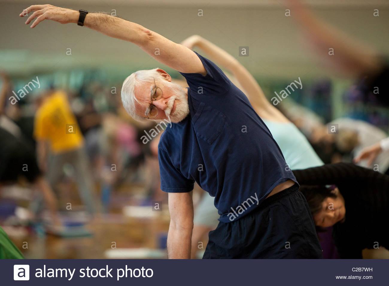 Un étirement latéral de poser dans un cours de yoga. Banque D'Images