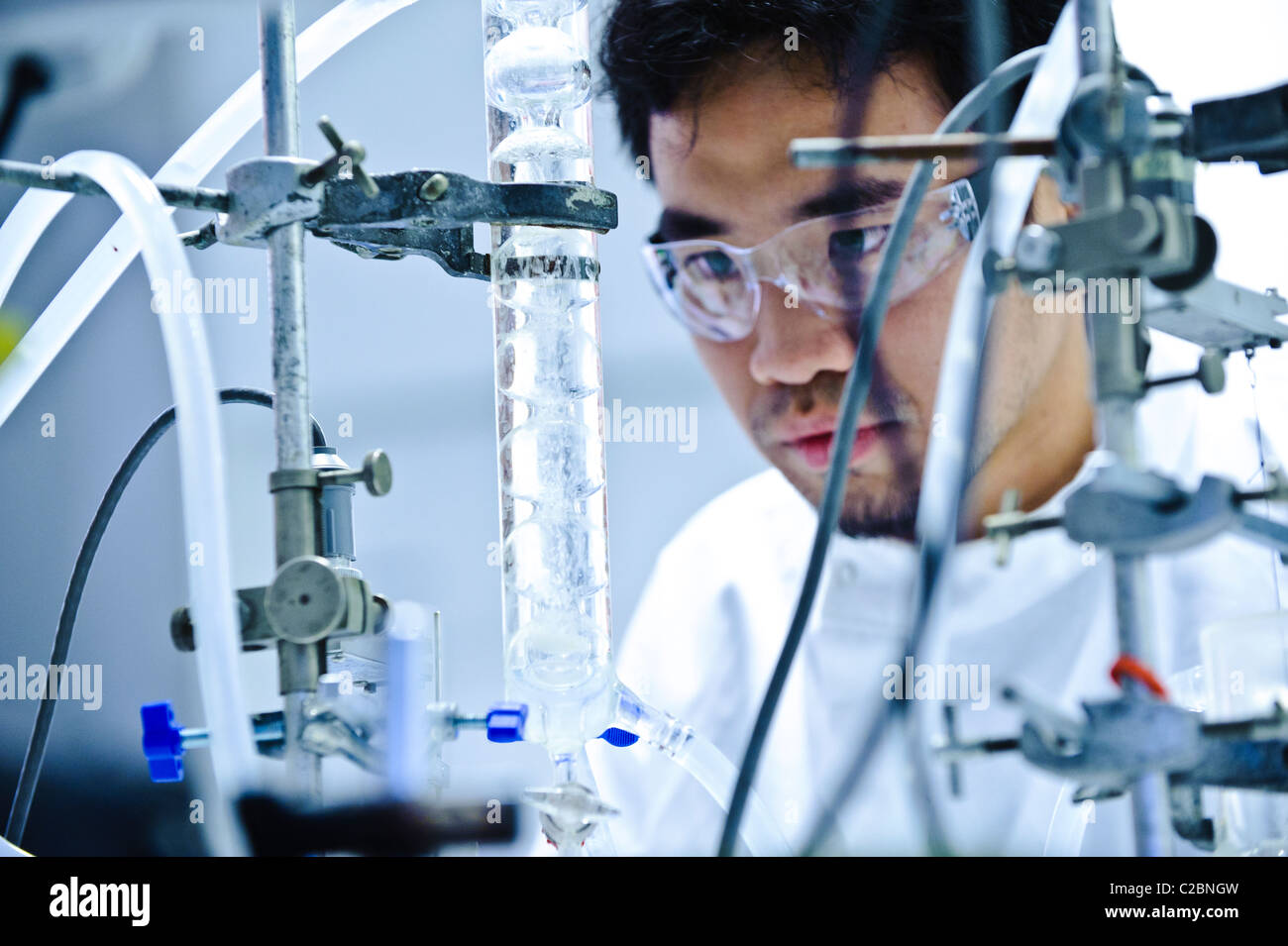 Young Asian male scientist portant des lunettes clair et blanc manteau la science à tube de verre à l'appareil Photo Stock
