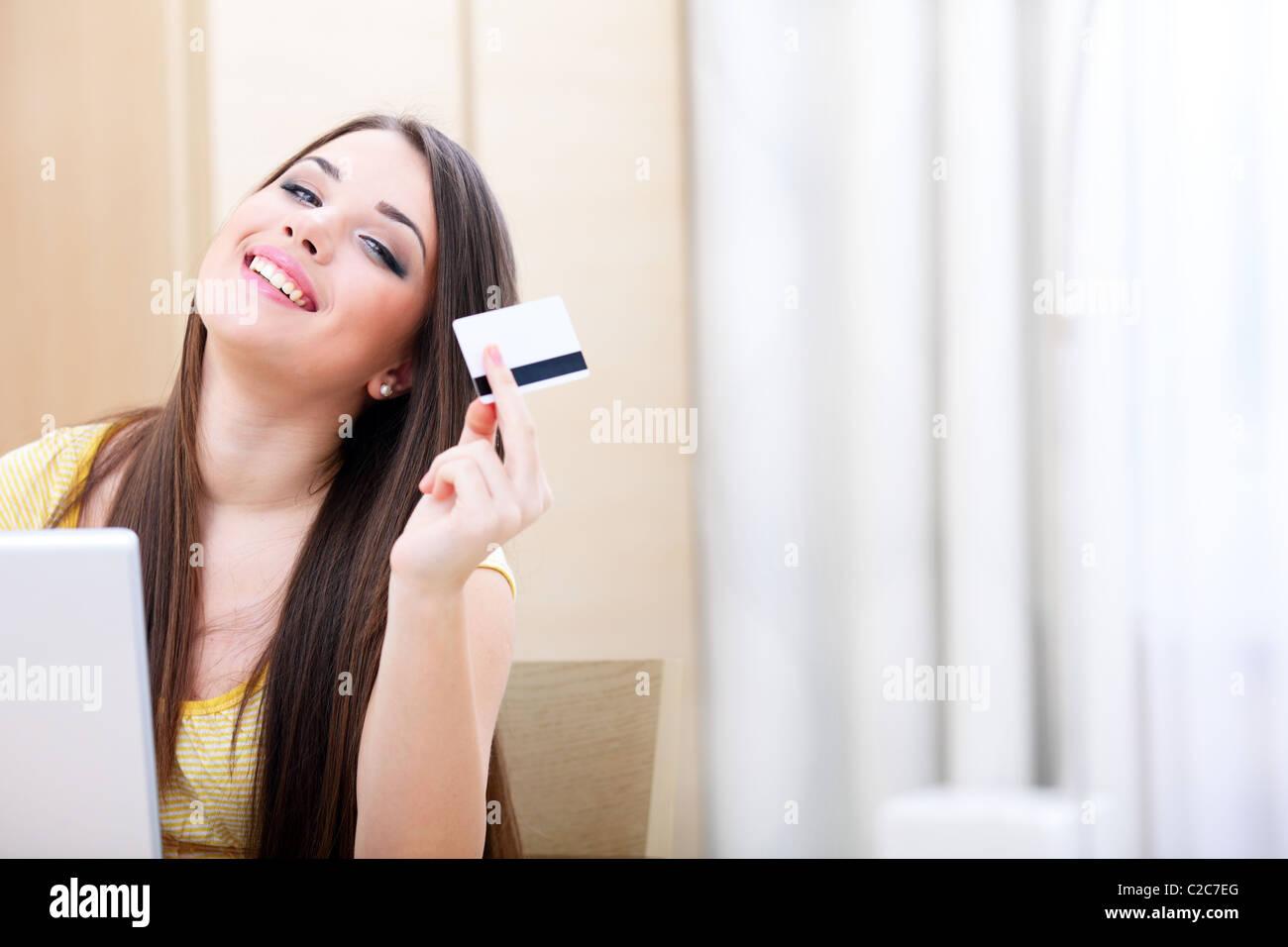 Belle jeune femme achats en ligne par carte de crédit et l'ordinateur portable Photo Stock