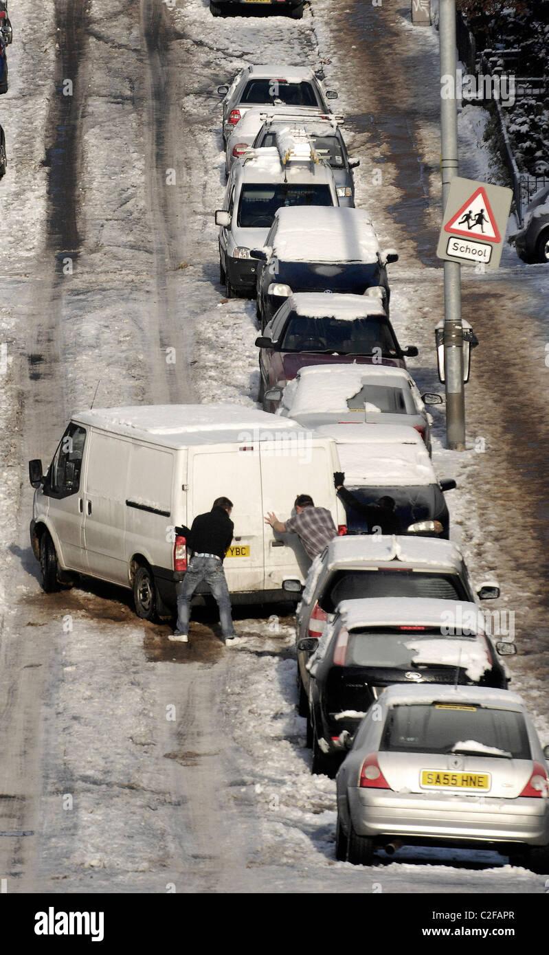 Deux hommes poussent un van sur une rue en pente, à Glasgow, en Écosse qui est recouverte de glace et Photo Stock