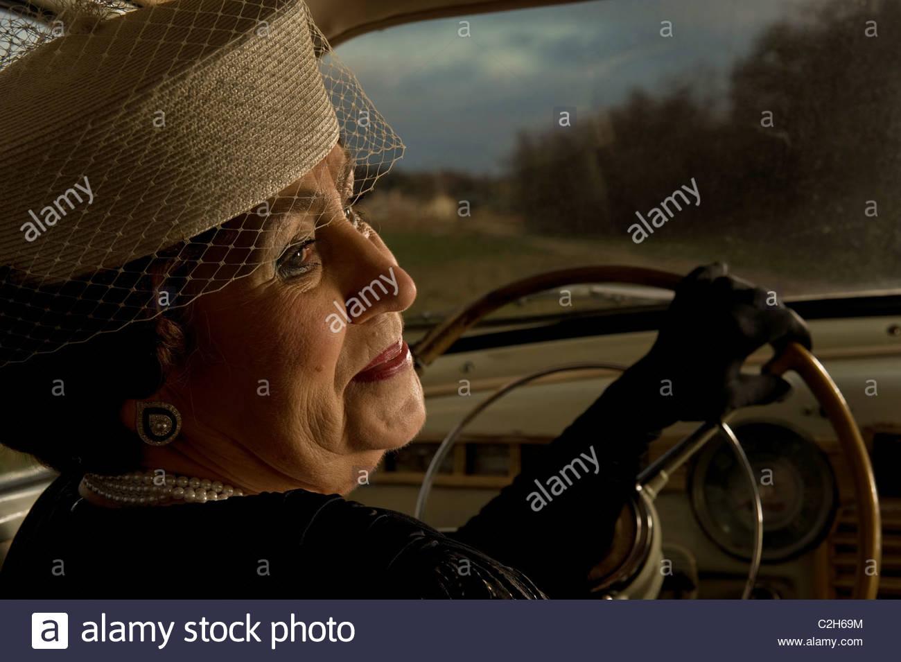 Femme Mature Senior est au volant d'une voiture d'époque Photo Stock