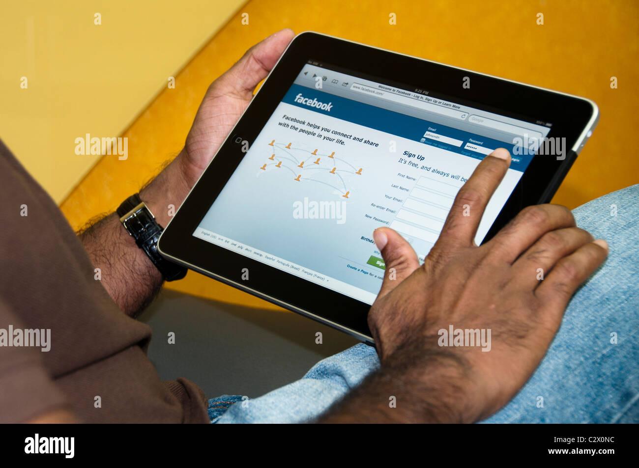 Vue rapprochée d'un homme à l'aide de Facebook avec l'iPad Photo Stock