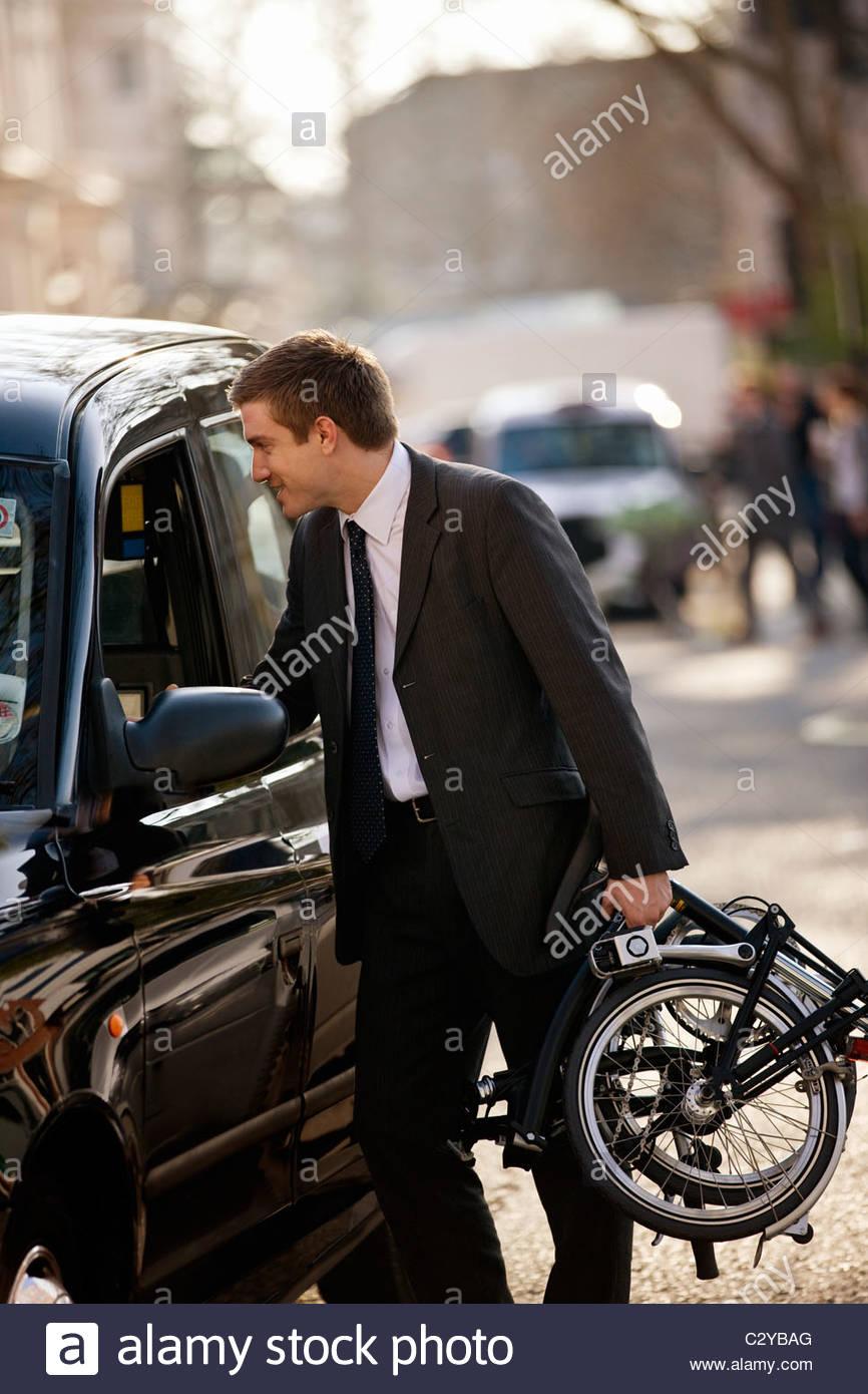 Un homme parlant à un chauffeur de taxi, portant son vélo plié Photo Stock