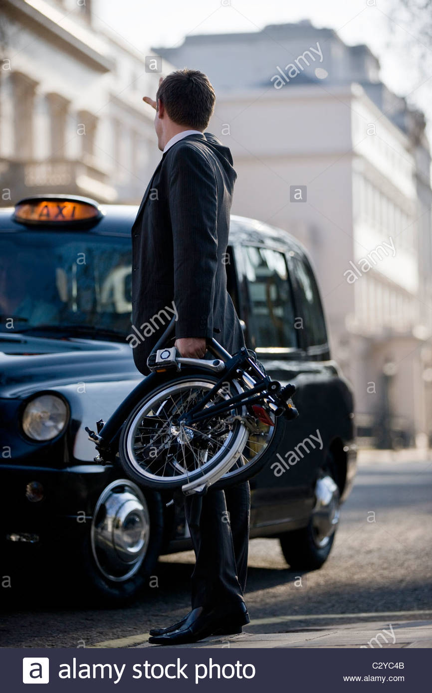 Un businessman hailing taxi, tenant son vélo plié Photo Stock