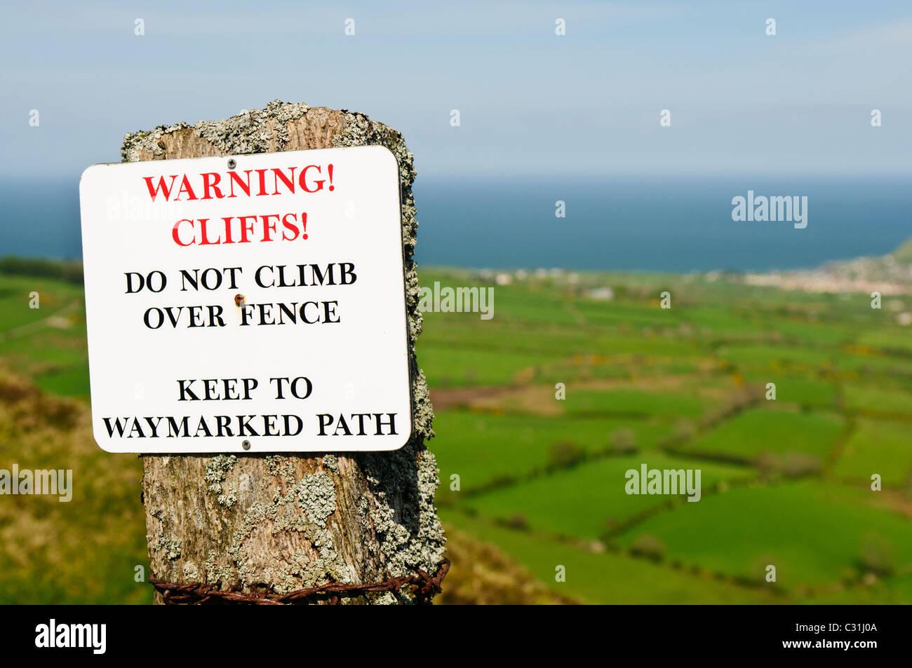Signer les marcheurs d'avertissement de ne pas escalader une clôture en raison d'un danger de hautes Photo Stock