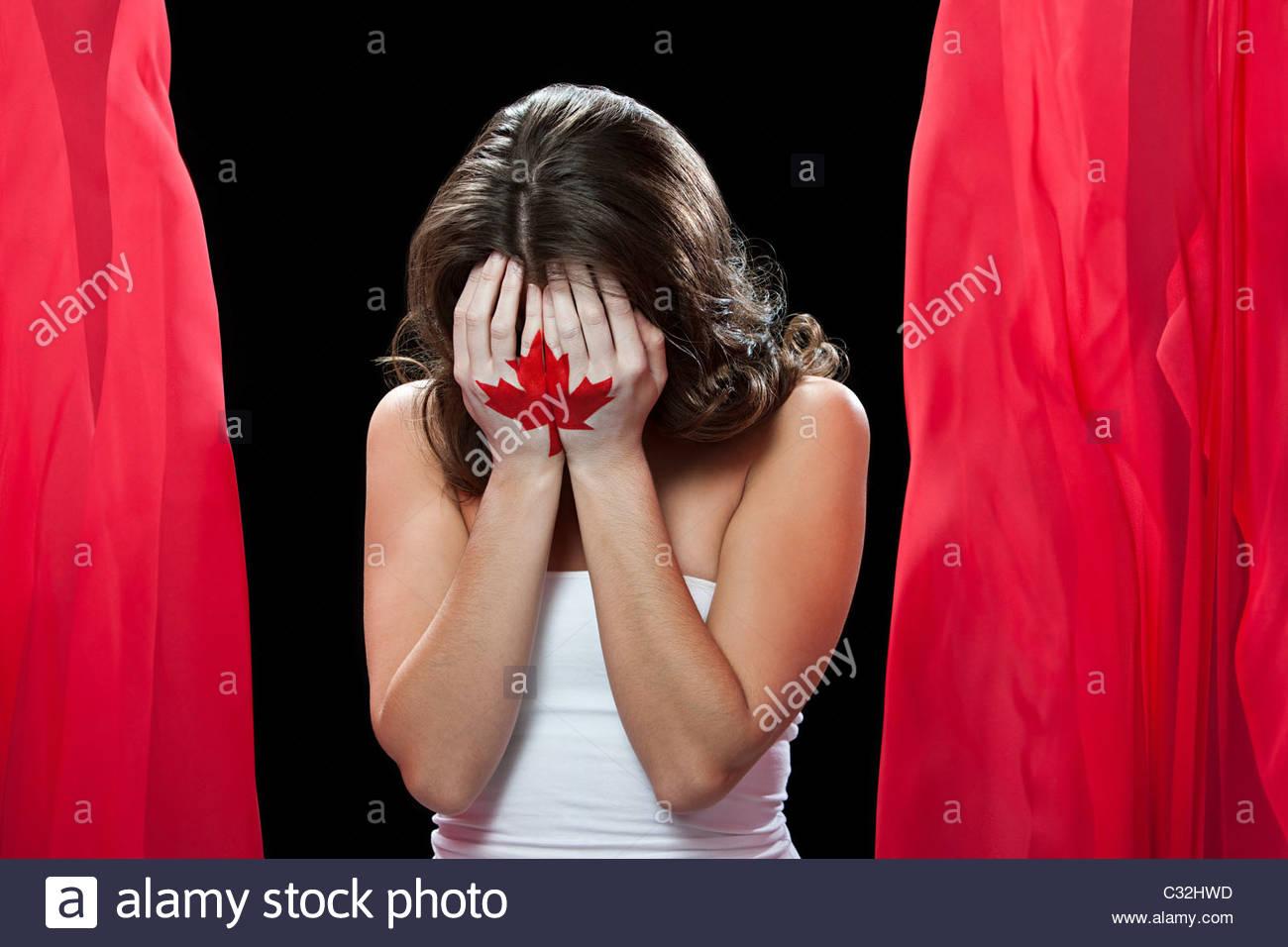 Femme avec feuille d'érable peint sur les mains, la tête dans les mains Photo Stock