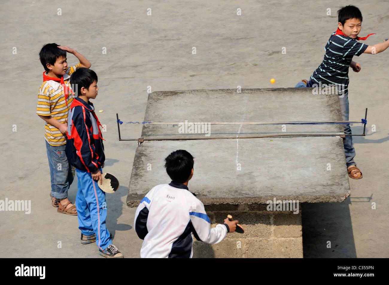 Les élèves de l'école primaire en Chine jouer au tennis de table dans la campagne dans le comté Photo Stock
