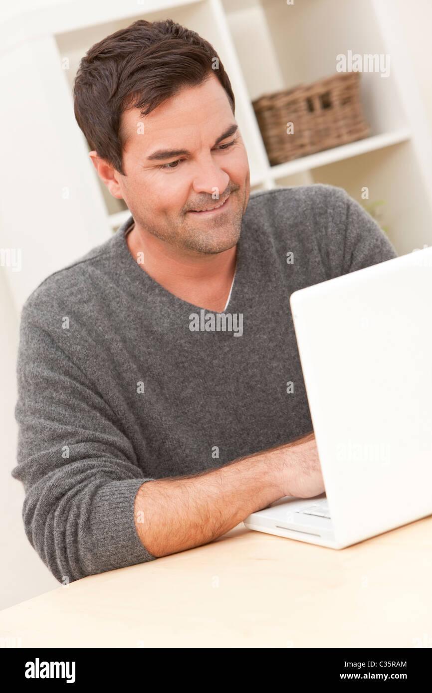 Couple dans la trentaine à la maison en utilisant son ordinateur portable Photo Stock