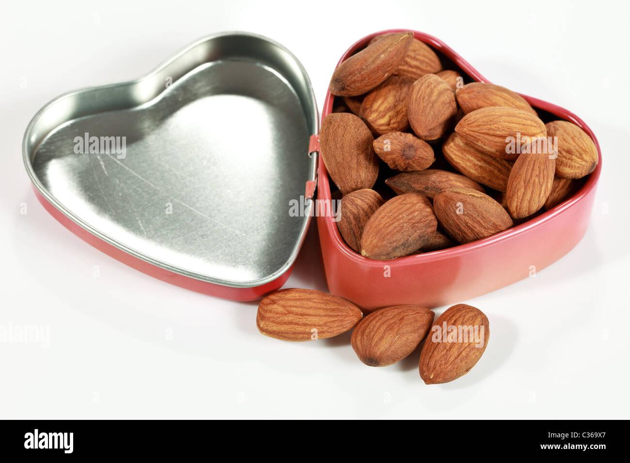 Amandes brutes dans une jolie boîte en forme de coeur les amandes sont une bonne indication de l'alimentation Photo Stock