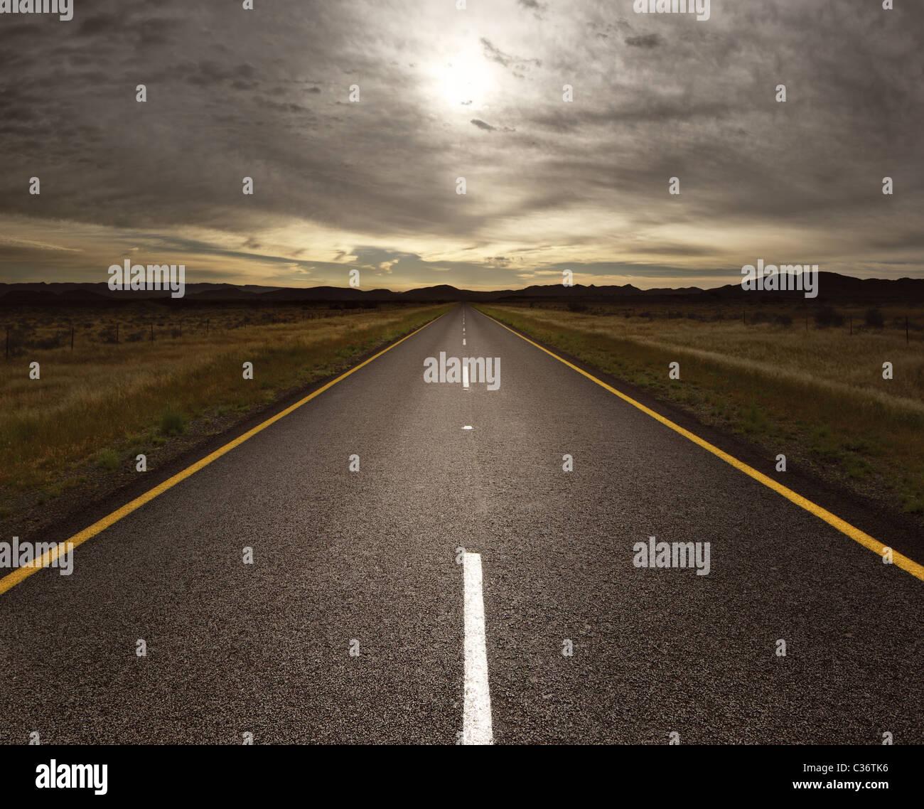 Tout droit route goudronnée menant à la lumière (image) tonique Photo Stock