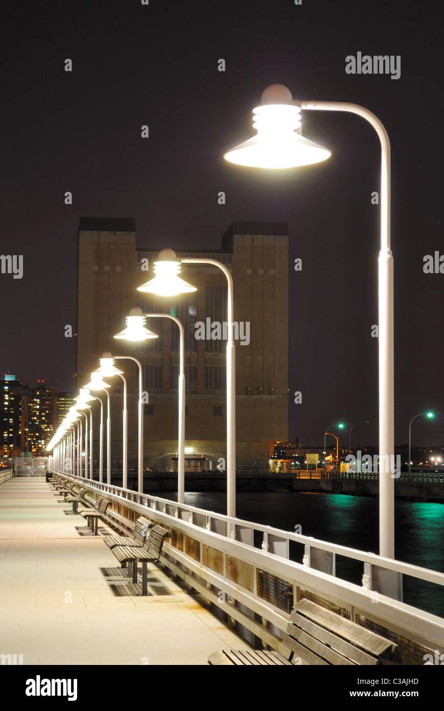 Longue jetée avec des lumières au loin. Photo Stock