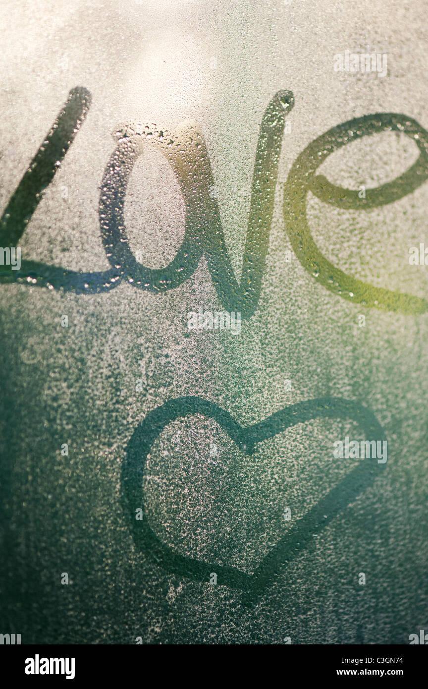 Amour écrit dans la condensation sur une vitre Photo Stock