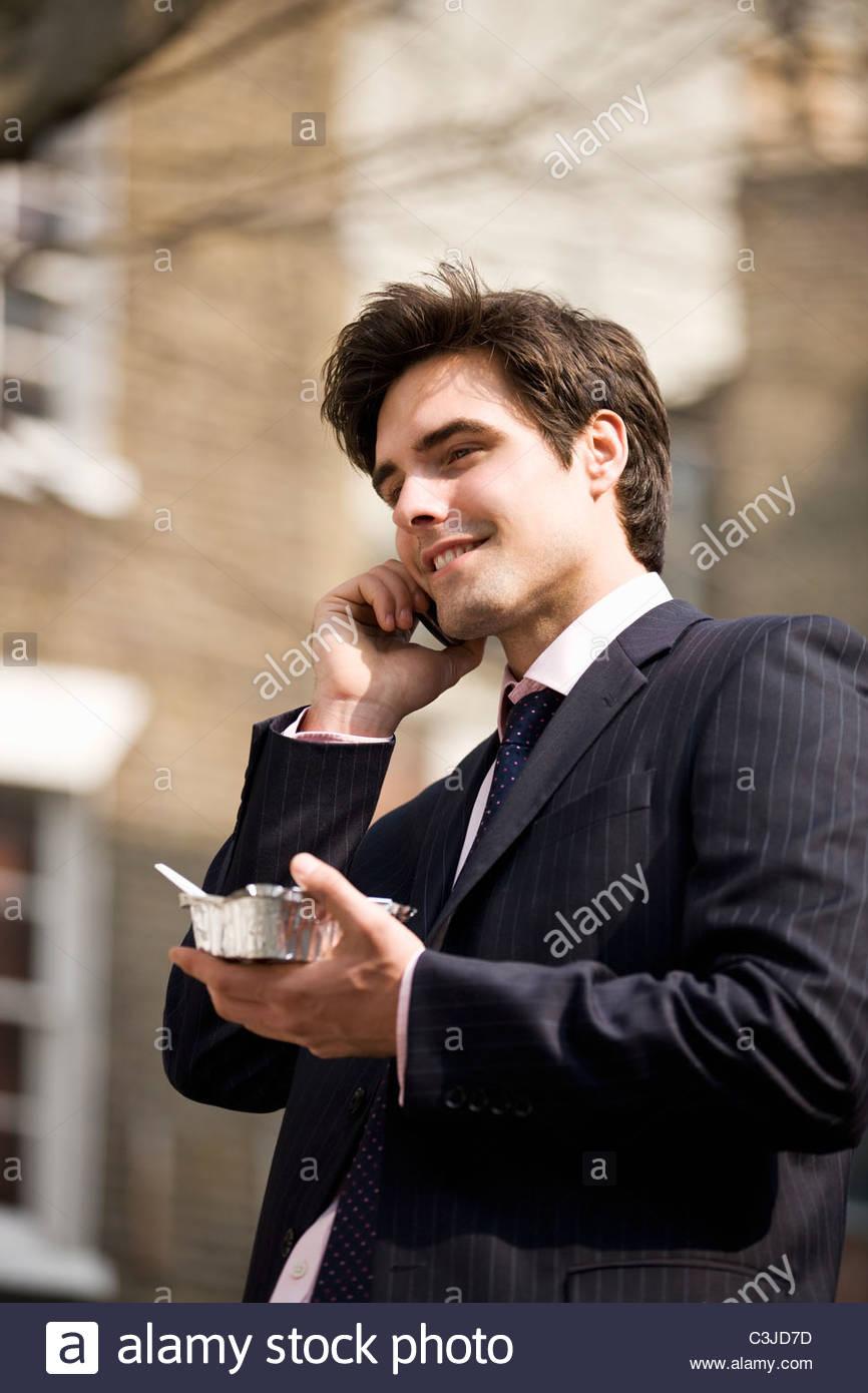 Un couple sur son téléphone mobile, de manger des plats à emporter Photo Stock