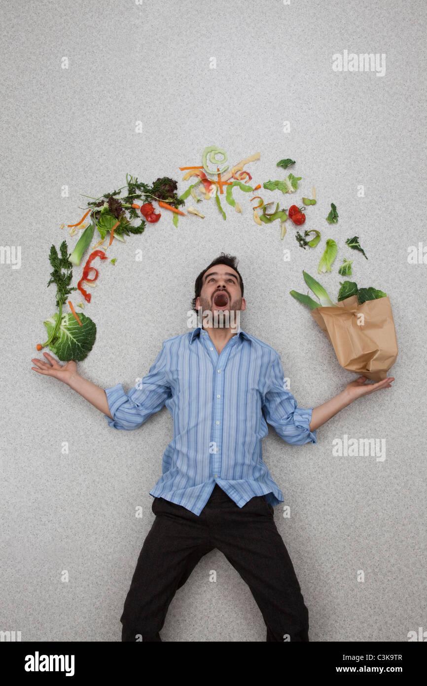 Mid adult man holding l'équilibre entre les légumes avec bouche ouverte Photo Stock