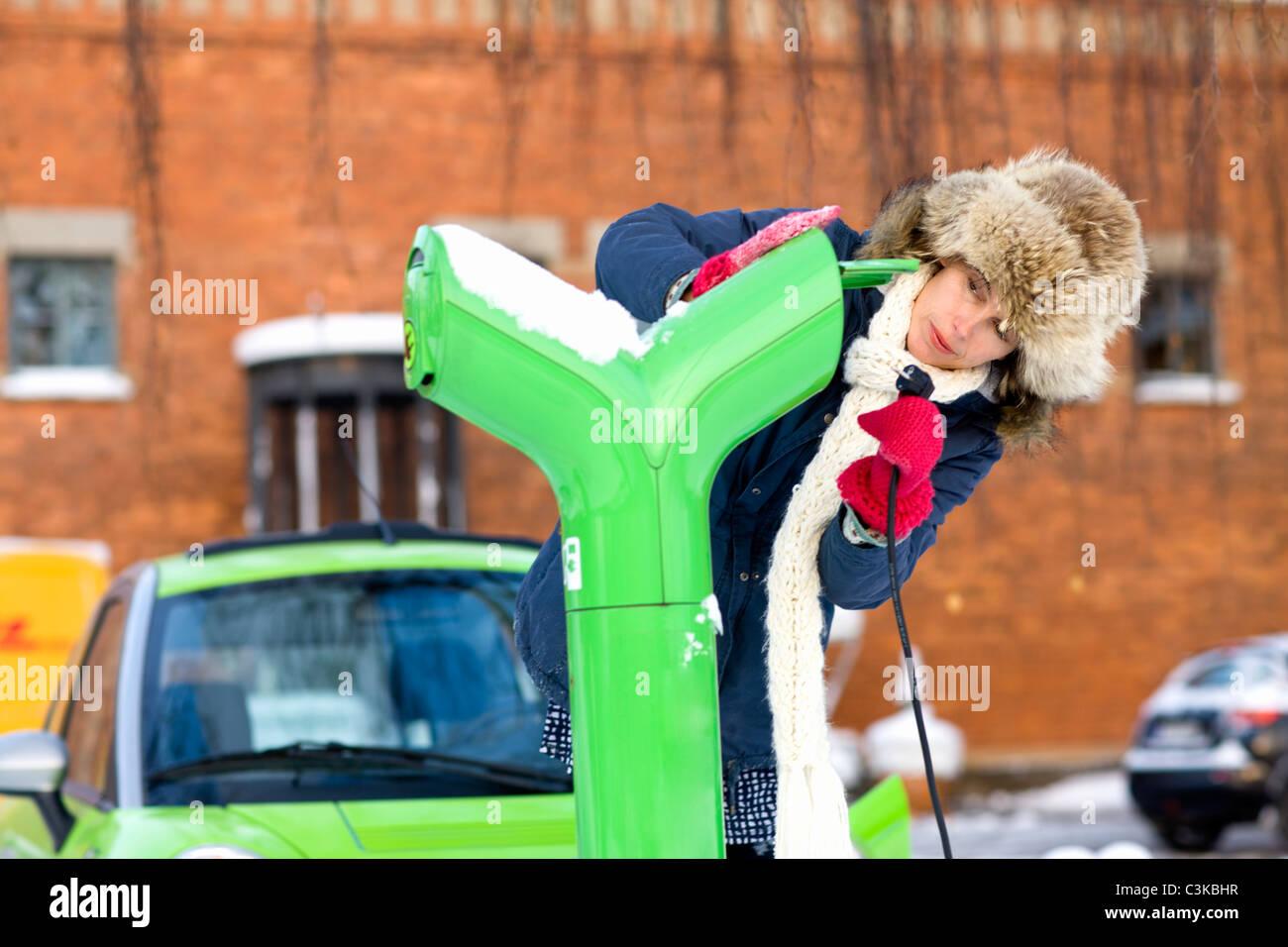 Jeune femme voiture électrique de charge Photo Stock